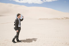 Man carrying water bottle in desert Stock Photo