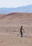 Man carrying water through desert Stock Photography