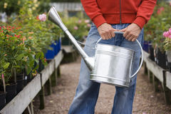 Man carrying watering can in garden centre, front view, mid-section, flowers in background Stock Photo