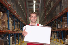Man carrying white box. A view of a young man carrying a white box as he works in a large warehouse stock photo