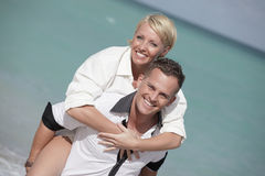 Man carrying with woman. Young male carrying a beautiful woman on his back at the beach Stock Photos