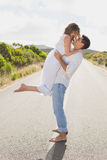 Man carrying woman on countryside road Stock Images