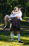 Man carrying woman on hands. Man in scottish costume carrying women on hands Royalty Free Stock Photography