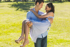 Man carrying a woman in park Stock Photography