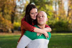 Man Carrying Woman Piggyback At Autumn Woods Royalty Free Stock Images