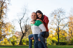 Man Carrying Woman Piggyback At Autumn Woods Royalty Free Stock Image