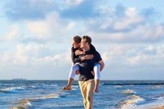 Man carrying woman piggyback at beach Stock Images
