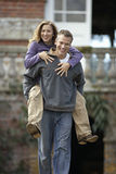 Man carrying woman by piggyback, smiling, front view, portrait. Man carrying women by piggyback, smiling, front view, portrait Royalty Free Stock Photography