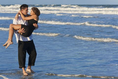 Man Carrying Woman in Romantic Embrace On Beach. A young man carrying his girlfriend as a romantic couple through the surf on a beautiful beach Royalty Free Stock Images