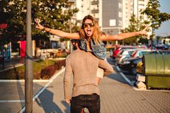Man carrying woman while she is showing tongue. Man carrying women while she is showing peace sign and her tongue Stock Image