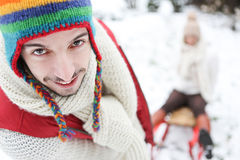 Man carrying woman in sled Royalty Free Stock Photography