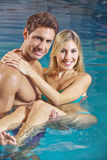 Man carrying woman in swimming pool Stock Photography