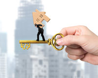 Man carrying wood house balancing on treasure key. In dollar sign shape with hand holding Stock Photography