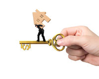 Man carrying wood house balancing on treasure key. In dollar sign shape with hand holding, isolated on white background Royalty Free Stock Image