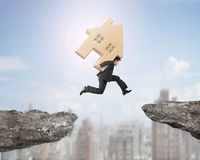 Man carrying wooden house jumping over two cliffs Royalty Free Stock Image