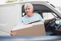 Man with carton box in front of van Stock Photos