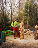 A man carves a hawk during christmas market. A man carves a hawk from a log during the christmas market in the town of Halsbach in Germany Royalty Free Stock Images