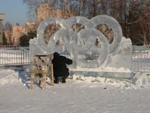 Man carves ice Olympic symbols Stock Images