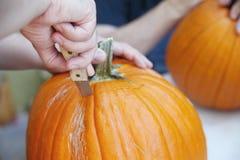 Man carves out  Halloween jack o' lantern lid Stock Photos