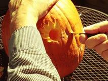 Man carves pumpkin at Halloween Stock Image