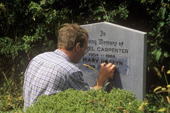 A man carving a gravestone at Kilcatherine Church in Cork, Ireland Royalty Free Stock Photography
