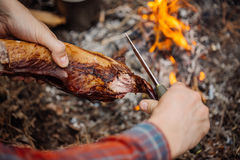 Man carving grilled rabbit meat in forest camp. Top view. stock image