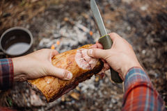 Man carving grilled rabbit meat in forest camp. Top view. Bushcraft concept royalty free stock image