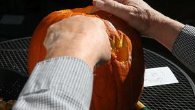 Man carving Halloween pumpkin stock video