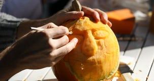 Man carving Helloween pumpkin stock footage