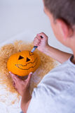 Man carving pumpkin Jack-O-Lantern for Halloween Stock Photography