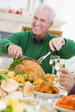 Man Carving Up Turkey At Christmas Dinner Royalty Free Stock Photo