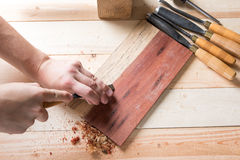 Man carving wood with handtools Stock Photos