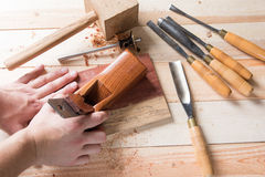 Man carving wood with handtools Stock Photo