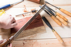 Man carving wood with handtools Stock Images