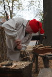 Man carving a wooden spoon historic garb Stock Image