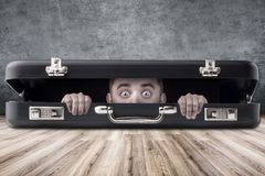 Man in a case. A man with big eyes looks out of a black case, the subject in the middle of the room stock images