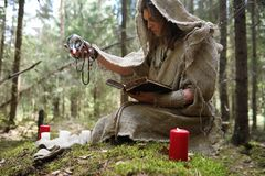 A man in a cassock spends a ritual in a dark forest. With a crystal ball and bookrr stock photo