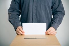 Man Casting His Vote. Blank envelope on which you can place your own text royalty free stock image