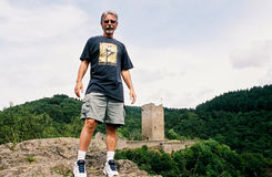 Man on Castle Hill. Image of a man standing on a mountain ledge in front of a German Castle Royalty Free Stock Images