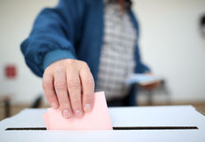 Man casts his ballot at elections. Man casts his ballot as he votes for the local elections at a polling station. Focus on hand Royalty Free Stock Photo