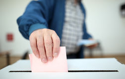 Man casts his ballot at elections stock photo
