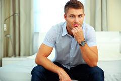 Man in casual cloth sitting on the bed Stock Photos
