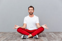 Man in casual cloth sitting in lotus position Stock Photo