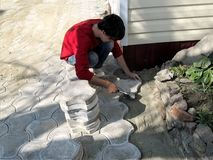 Man in casual clothes does work on laying paving slabs, top view. Young adult dark-haired worker knocks a rubber mallet on a tile. Setting it in a dry sand royalty free stock image