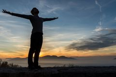 Man in casual clothes with his arms spread widely standing outdo. Ors silhouetted against a sunrise with the fiery sun peeping over mountains Stock Image