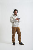 Man in casual clothes with phone and headphones Stock Photography