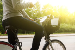 Man in casual clothes riding bike and focuses on phone Royalty Free Stock Image