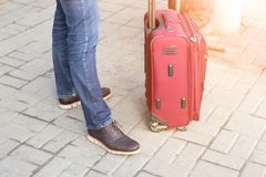 Man in casual clothes standing with red suitcase at station. Young modern traveller waiting for dealyed trip. Person with luggage. Starting journey Royalty Free Stock Photography