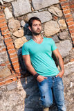Man in casual clothes stands against a brick rock wall Royalty Free Stock Photography
