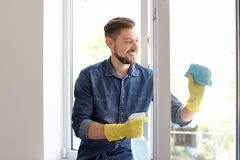Man washing window glass at home. Man in casual clothes washing window glass at home Stock Photography